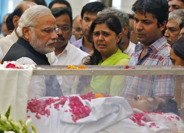 Modi looks at the casket of Munde, next to Munde's daughter, at BJP headquarters in New Delhi