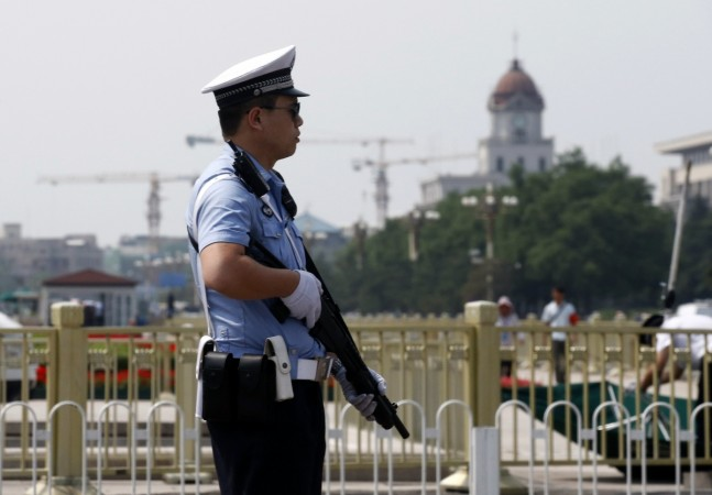 Policeman stands guard with a shotgun in front of Tiananmen Square in Beijing