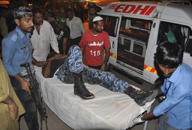An ASF soldier leads a colleague on a stretcher, who was wounded in an attack at Jinnah International Airport, outside Jinnah hospital in Karachi