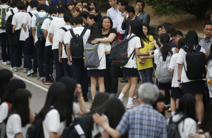 Relatives of the April 16 ferry disaster victims comfort students who survived the accident as they make their way back to school in Ansan