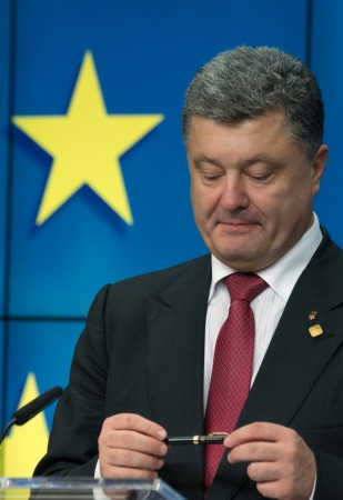 Ukraine's President Poroshenko holds pen, which ousted predecessor was due to use to sign same agreement on Nov. 29, 2013 at the EU Council in Brussels