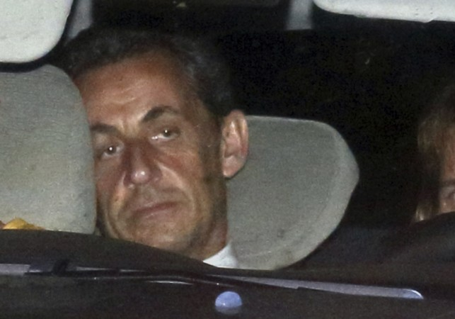 Former French President Nicolas Sarkozy arrives with police by car at the financial investigation unit in Paris to be presented to a judge