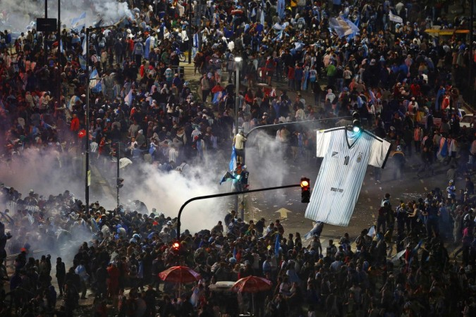 Argentina's fans run away from tear gas as they clash with riot police in Buenos Aires after Argentina lost to Germany in their 2014 World Cup final match in Brazil