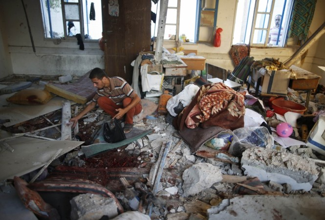 Palestinians collect the remains of bodies at a United Nation-run school sheltering Palestinians displaced by an Israeli ground offensive, that witnesses said was hit by Israeli shelling, in Jebalya refugee camp in the northern Gaza Strip