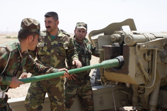 Kurdish Peshmerga troops prepare to fire a cannon during clashes with militants of the Islamic State in Iraq