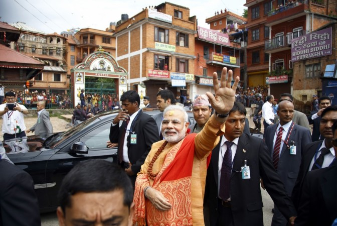 India's Prime Minister Narendra Modi waves at supporters waiting to greet him at the premises of Pashupatinath Temple in Kathmandu August 4, 2014
