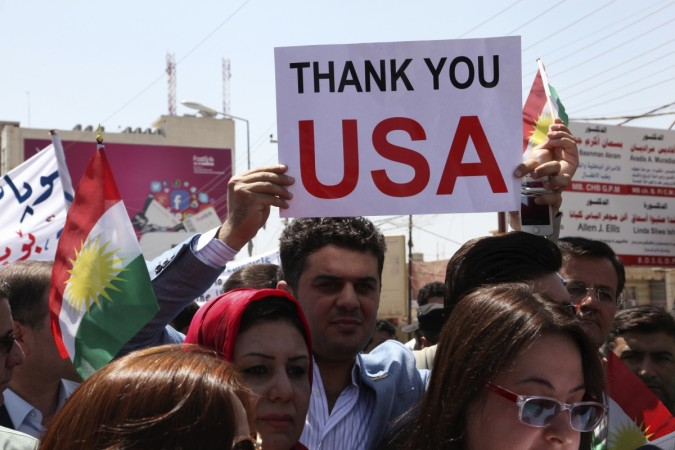 A Kurdish resident holds a signs during a demonstration in support of the Peshmerga troops in front of the U.S. consulate in Arbil, north of Baghdad,