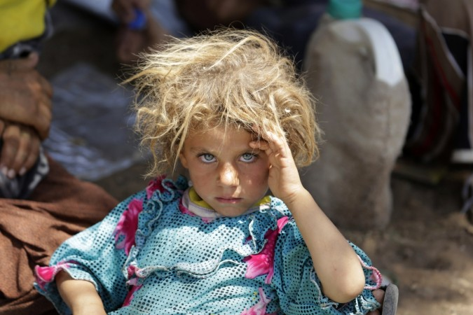 A child from the minority Yazidi sect, fleeing the violence in the Iraqi town of Sinjar, rests at the Iraqi-Syrian border crossing in Fishkhabour, Dohuk province.