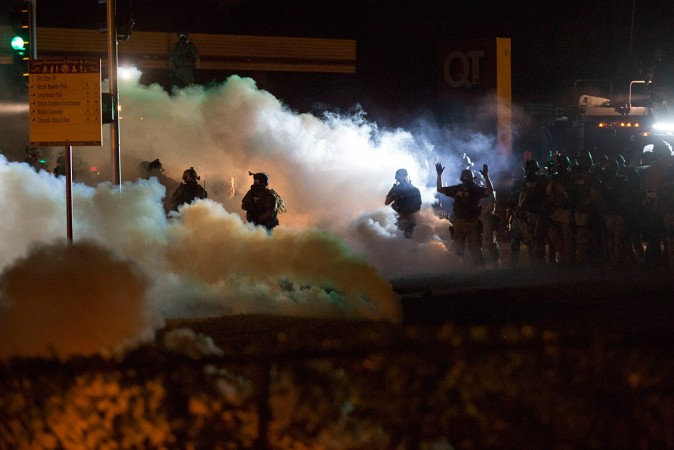Riot police clear a street with smoke bombs while clashing with demonstrators in Ferguson