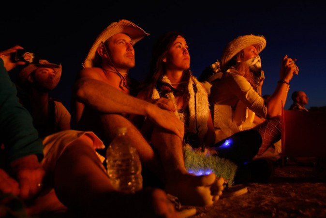 Festival-goers watch as the effigy of The Burning man lights up after the fireworks