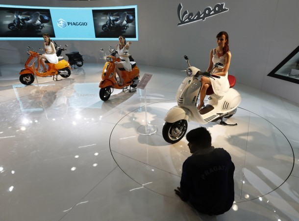 Models sit on scooters at the Vespa pavilion as a worker cleans the floor during the Indian Auto Expo in Greater Noida.