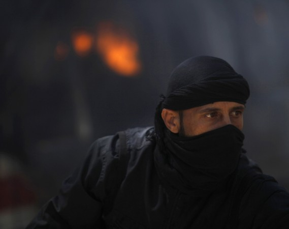A fighter from the Islamist Syrian rebel group Jabhat al-Nusra is seen in front of a burning vehicle.