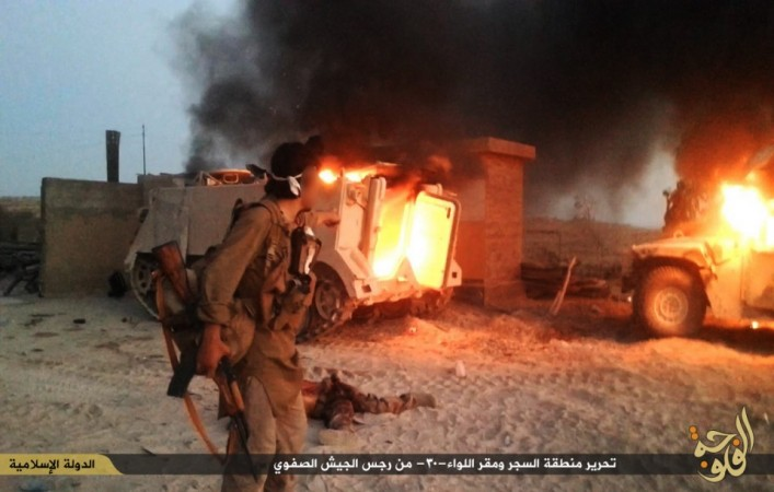 An ISIS fighter looks at a destroyed M113 armored personnel carrier