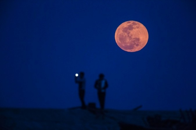 Observers take picture during a blood moon rising in Shanghai.