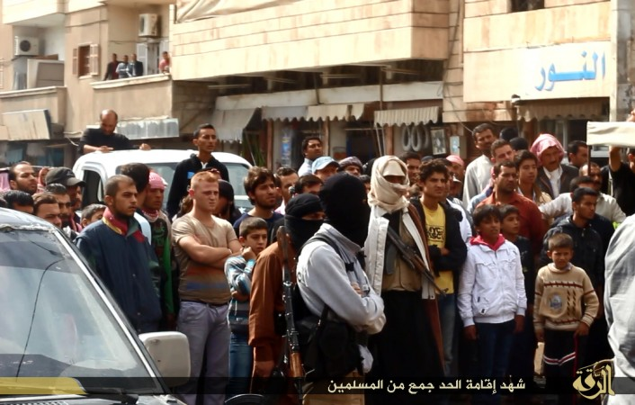 People gather to watch the beheading of three men accused by ISIS of insulting Allah in Raqqa.