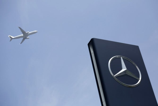A plane flies above as a Mercedes-Benz logo is seen outside its Shanghai office, August 5, 2014.