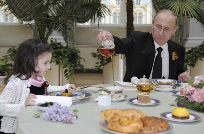 President Putin serving a cup of tea to a young girl