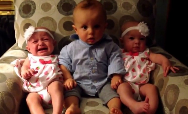 The video showing the comical moment a baby boy gets into a spin as he encounters twins for the first time.