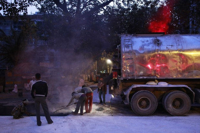 Labourers work during the early morning at the construction site of a road in Mumbai January 2, 2015.