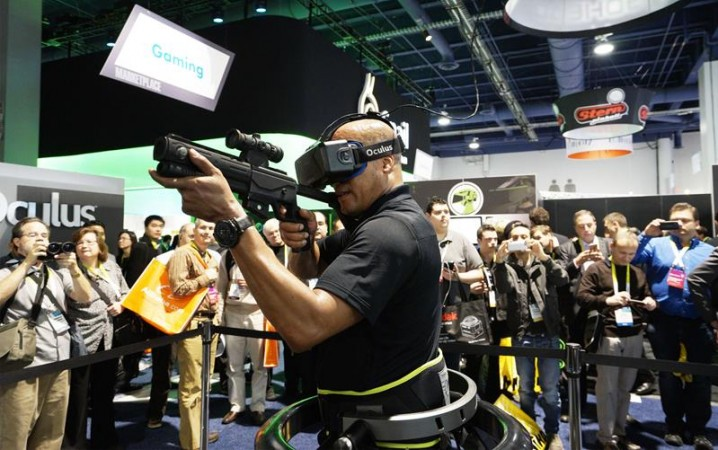 A man wearing an Oculus VR headset demonstrates a first person shooter game in a Virtuix Omni virtual reality system at the International Consumer Electronics show