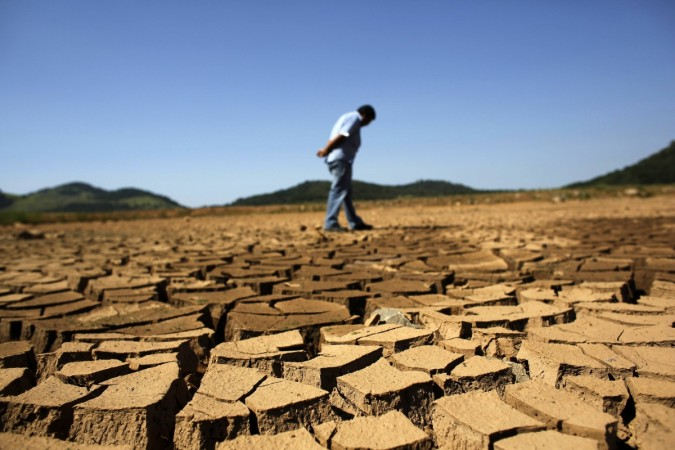 A worker from the Sao Paulo state company that provides water and sewage services to residential, commercial and industrial areas looks at the cracked ground of near Jaguary dam in Braganca Paulista, 100 km from Sao Paulo, in this file photo taken January