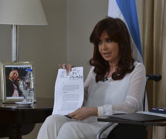 Argentina's President Cristina Fernandez de Kirchner shows a document as she addresses the nation during a televised speech in Buenos Aires, January 26, 2015.