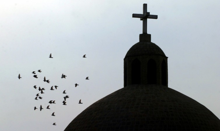 A flock of birds flies past a cross atop a Christian church in Baghdad