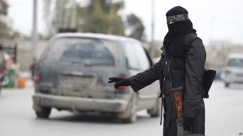 A lady guard working for a Islamist radical group stands at a check point in Syria