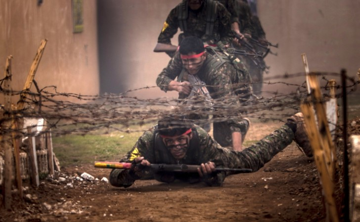 Fighters of the Kurdish People's Protection Units (YPG) crawl under barbed wires with their weapons at a military training camp in Ras al-Ain February 13, 2015.