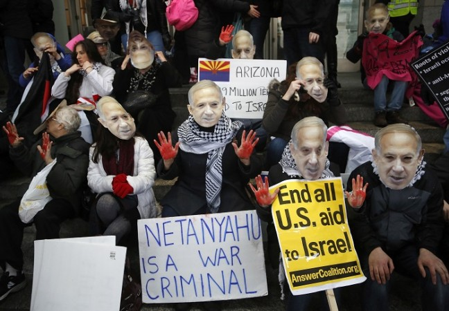 Anti-Israel demonstrators led by the protest group Code Pink wear masks of Israeli Prime Benjamin Netanyahu as they sit at the entrance to the American Israel Public Affairs Committee (AIPAC) policy conference at the Washington Convention Center in Washin
