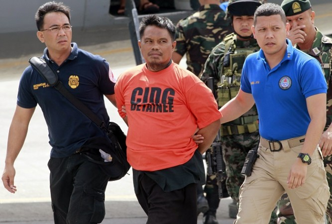 Members of the Philippine National Police (PNP) intelligence escort Mohammad Ali Tambako (C), founder and leader of the Justice Islamic Movement, upon arrival at Villamor Air Base in Manila March 16, 2015.
