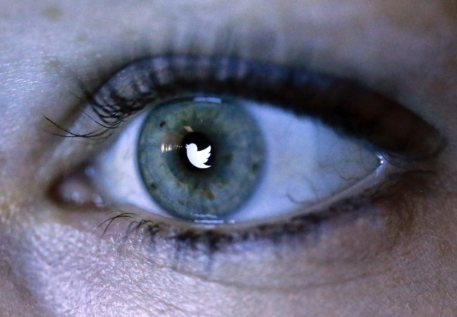 An illustration picture shows the Twitter logo reflected in the eye of a woman.