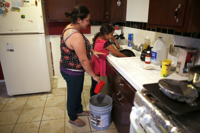 Marisela Corona, 26, (L) whose well has run dry, washes dishes with her daughter Andrea Andrade Corona, 8, from a water bucket in Porterville, California October 14, 2014.