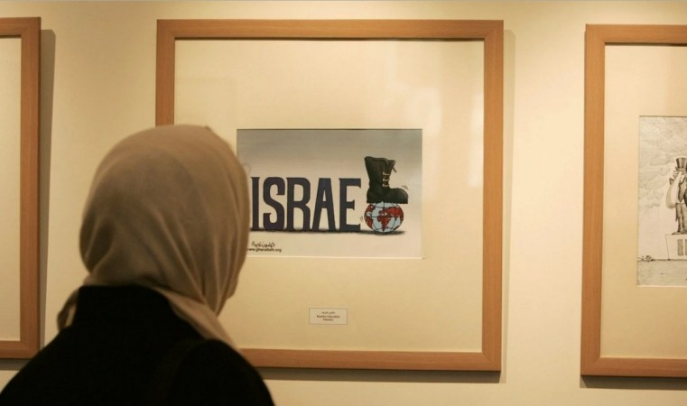 An Iranian woman looks at an entry from the International Holocaust Cartoon Contest in Tehran on Aug. 14, 2006. (Raheb Homavandi/Reuters)