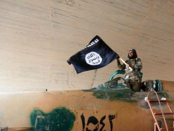 An Isis fighter waves the black flag of the Islamic State militant group standing inside the cockpit of a Syrian fighter plane.