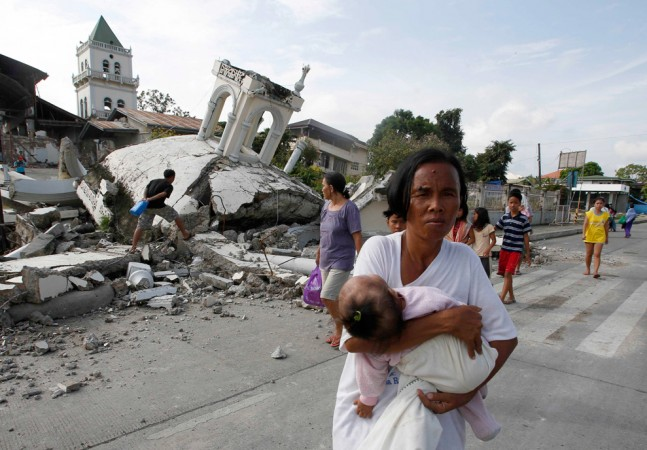 A woman carries her baby past a destroyed church belfry in Tubigon, Bohol on Oct. 16, a day after an earthquake hit central Philippines.