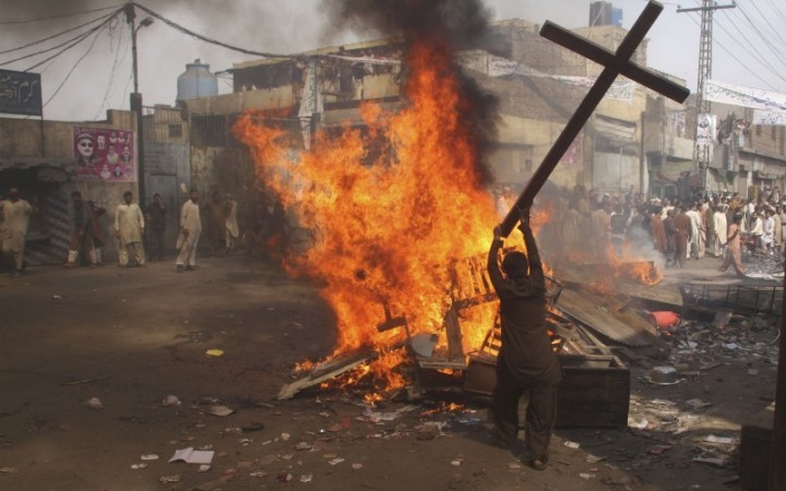 A demonstrator burns a cross during a protest in the Badami Bagh area of Lahore, Pakistan