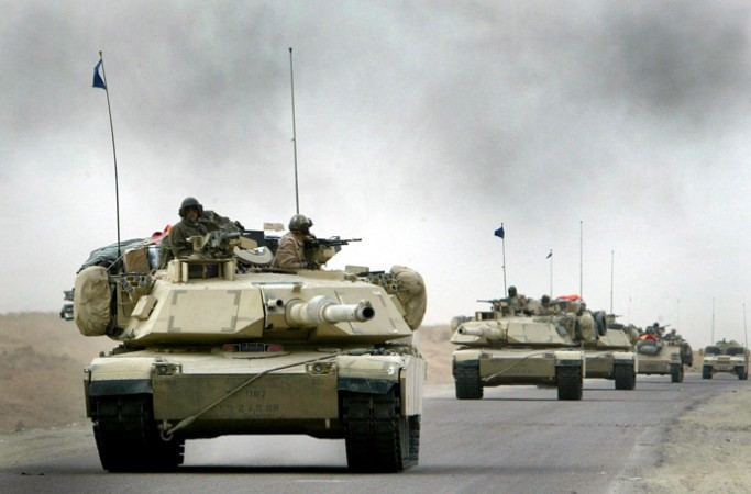 A convoy of US Army 3rd Infantry M1A1 Abrams tanks cross the Euphrates river as black smoke rises after an explosion as hundreds of armored vehicles push towards the outskirts of Baghdad on April 6, 2003.