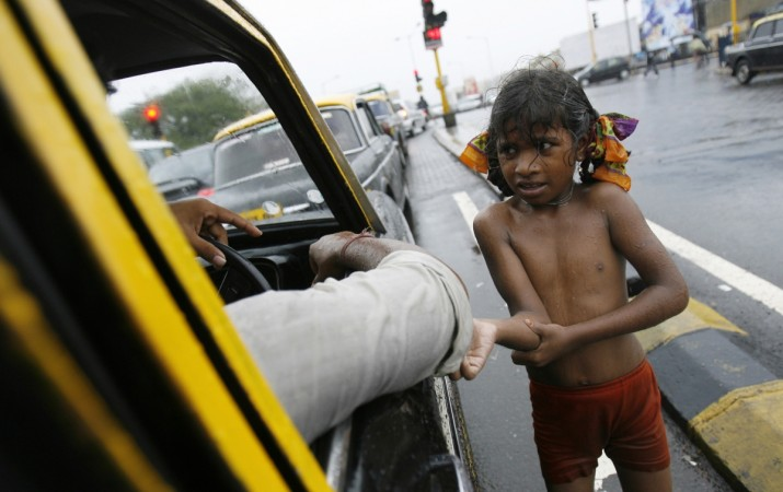 A girl begs for alms in India.