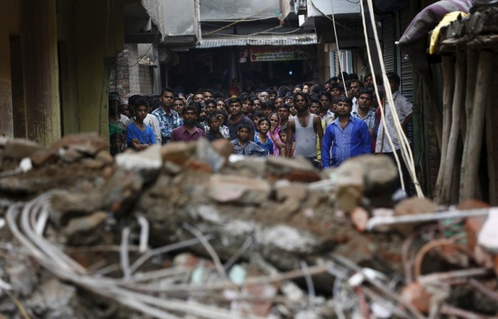 People looking on at the rubble of a collapsed building.