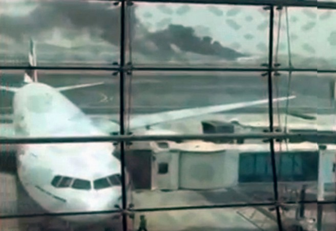 A still picture taken from an amateur video shows smoke rising (at rear) after an Emirates Airline flight crash-landed at Dubai International Airport, the UAE Aug. 3, 2016.