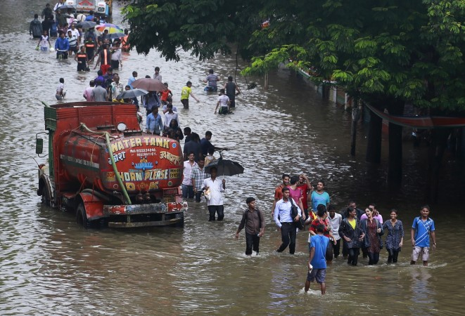 People walk through a flooded road as a water tanker is seen stuck due to heavy rains in Mumbai, India, June 19, 2015