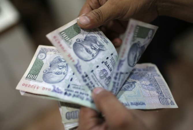 An employee counts Indian rupee currency notes inside a private money exchange office in New Delhi July 5, 2013