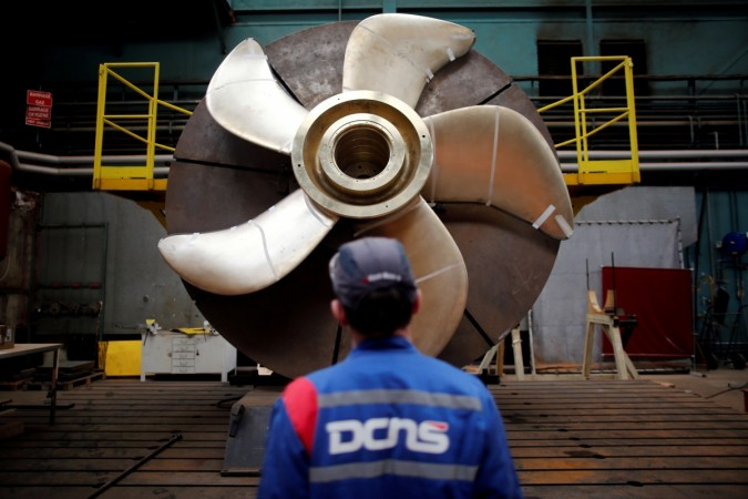 An employee looks at the propeller of a Scorpene submarine at the industrial site of the naval defence company and shipbuilder DCNS in La Montagne near Nantes, France, April 26, 2016.