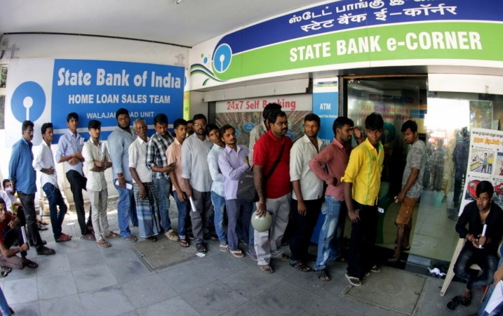 People wait to withdraw money from ATMs