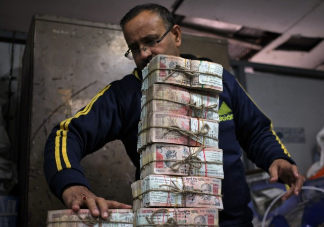 A bank employee stacks banned Rs 1,000 notes.