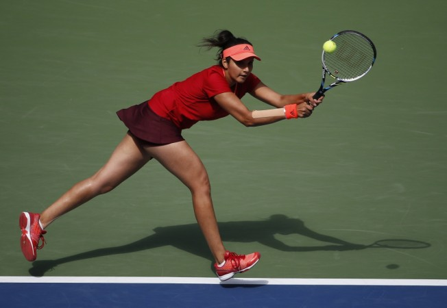 Sania Mirza of India chases down a return with playing partner Martina Hingis of Switzerland (not pictured) as they face Casey Dellacqua of Australia and Yaroslava Shvedova of Kazakhstan in the women's doubles final match at the U.S. Open Championships te
