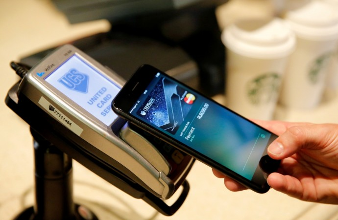 A man uses an iPhone 7 smartphone to demonstrate the mobile payment service Apple Pay