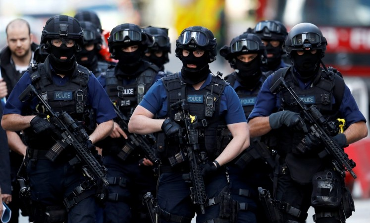 Armed police officers walk near Borough Market after the attack