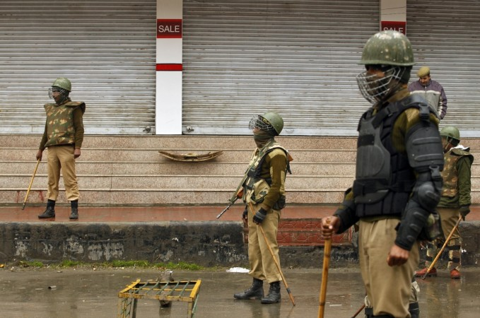 Indian policemen stand guard at a barricade setup during curfew of an area in Srinagar